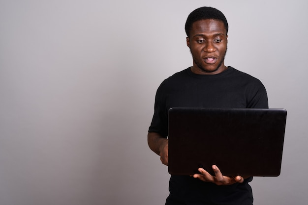 Junger afrikanischer mann, der schwarzes hemd auf grau trägt