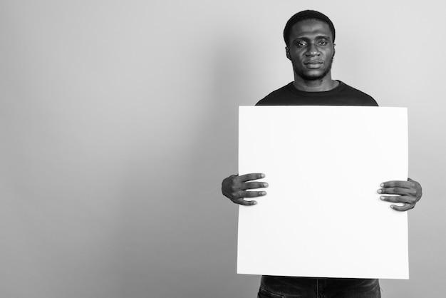 Junger afrikanischer mann, der schwarzes hemd trägt. schwarz und weiß