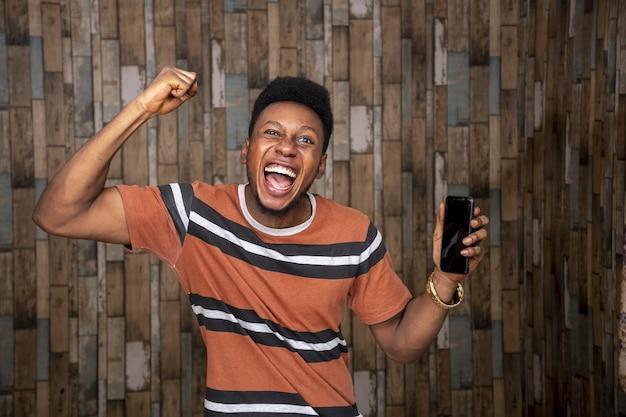 Junger afrikanischer mann, der sich über sein telefon aufregt, während er es freudig hält