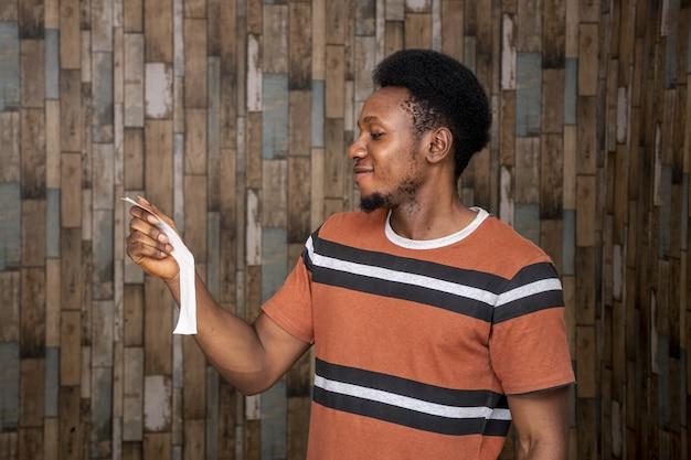 Junger afrikanischer mann, der sich von dem, was er auf dem zettel las, unsicher fühlt