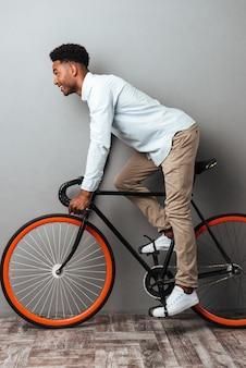 Junger afrikanischer mann, der über graue wand mit fahrrad steht.