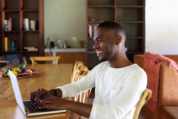 Junger afrikanischer mann, der zuhause an laptop arbeitet