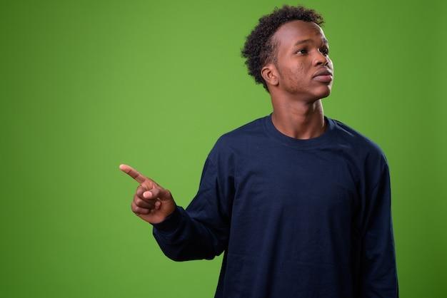 Junger afrikanischer mann gegen grüne wand