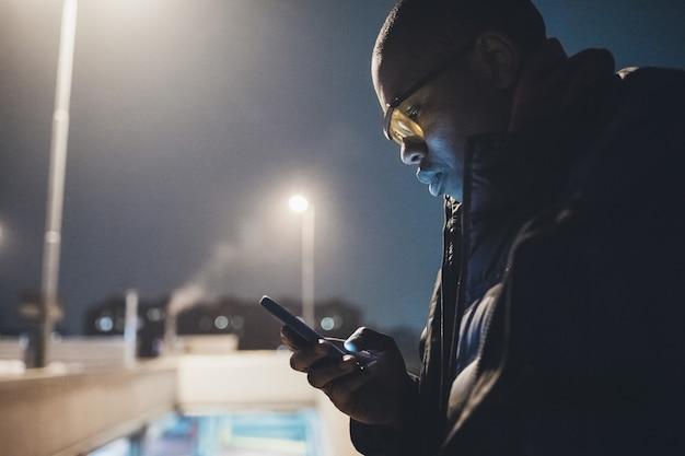 Junger afrikanischer mann im freien unter verwendung des smartphone