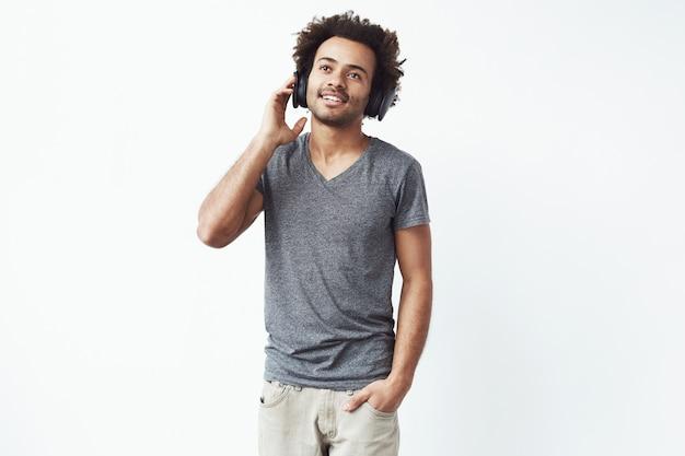 Junger afrikanischer mann in den kopfhörern, die optimistische musik hören