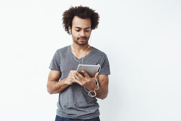 Junger afrikanischer mann in den kopfhörern, die tablette betrachten.