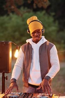 Junger afrikanischer mann in der stilvollen freizeitkleidung und in den kopfhörern, die geräusche auf plattenspielern mischen, während sie durch tisch mit stereoboard draußen stehen
