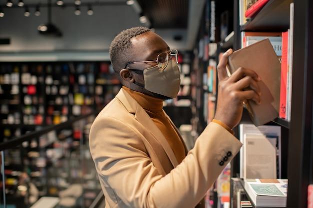 Junger afrikanischer mann in smart casualwear, der bücher in der bibliothek auswählt