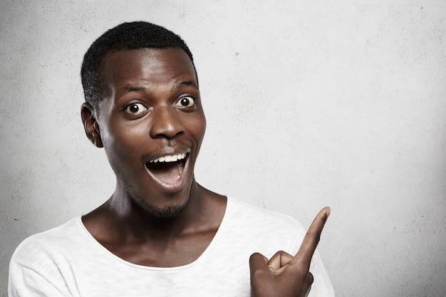 Junger afrikanischer mann in weißem t-shirt, der überrascht seinen mund weit öffnet, schockiert von hohen verkaufspreisen aussieht und etwas mit seinem finger an der leeren wand zeigt.