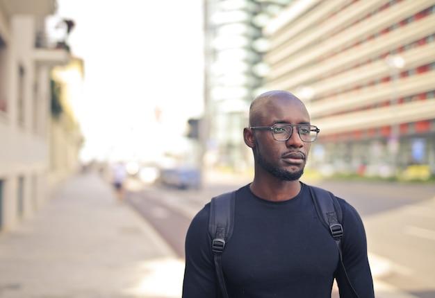 Junger afrikanischer mann mit brille, die ein schwarzes t-shirt und einen rucksack in der straße trägt