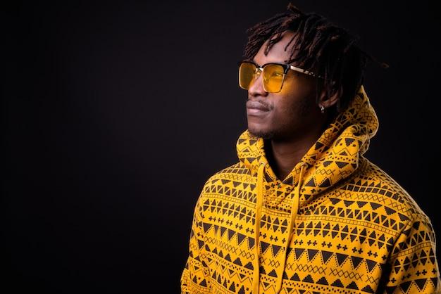 Junger afrikanischer mann mit dreadlocks auf schwarz