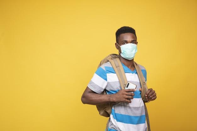 Junger afrikanischer mann mit einem rucksack, der eine gesichtsmaske trägt - covid-19