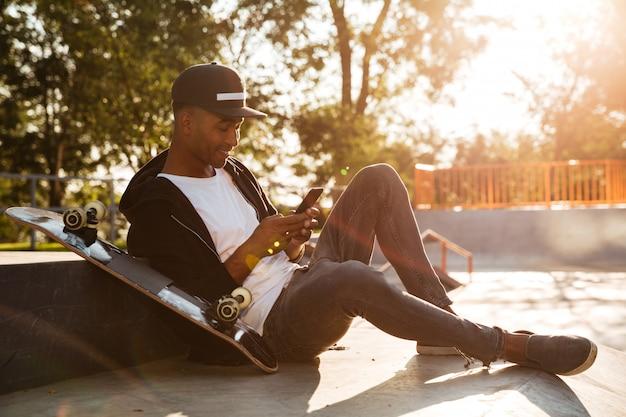 Junger afrikanischer mann mit einem skateboard unter verwendung des smartphones