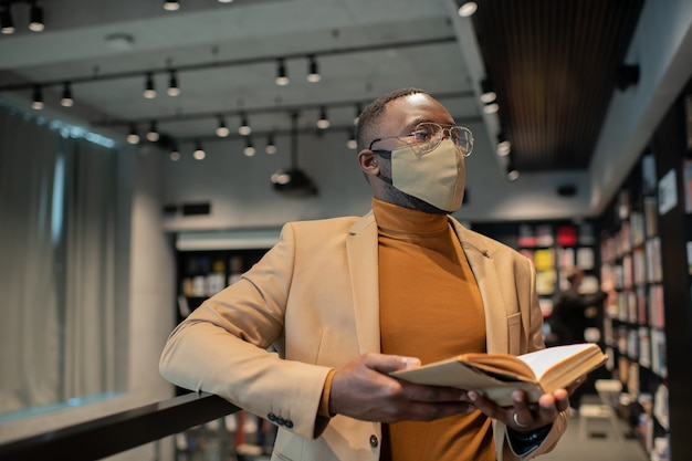 Junger afrikanischer mann mit offenem buch, das sich mit viel literatur anschaut