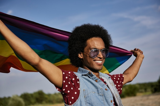 Junger afrikanischer mann mit regenbogenfahne, der am strand steht