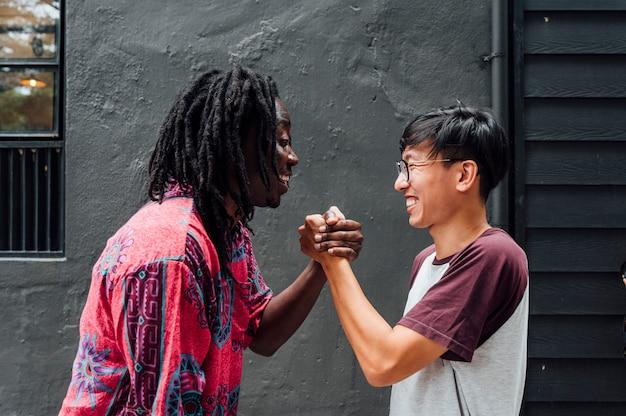 Junger afrikanischer mann und junger asiatischer mann fassen ihre hände