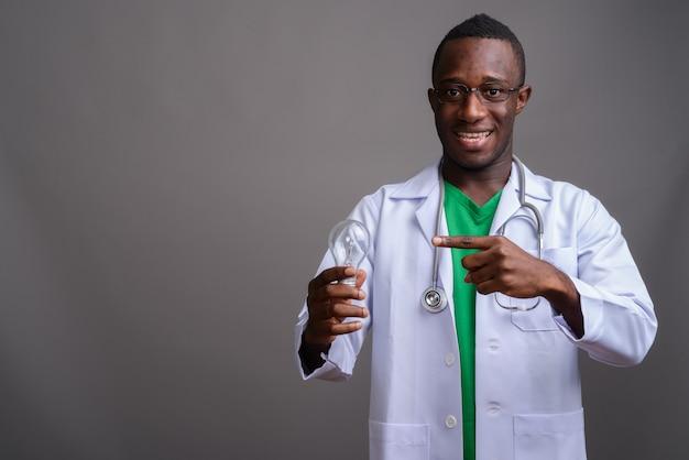 Junger afrikanischer mannarzt, der brillen auf grauer wand trägt