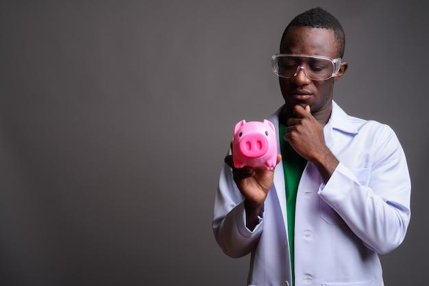 Junger afrikanischer mannarzt, der schutzbrille auf grauer wand trägt