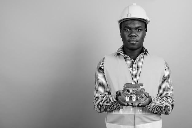 Junger afrikanischer mannbauarbeiter gegen weiße wand. schwarz und weiß