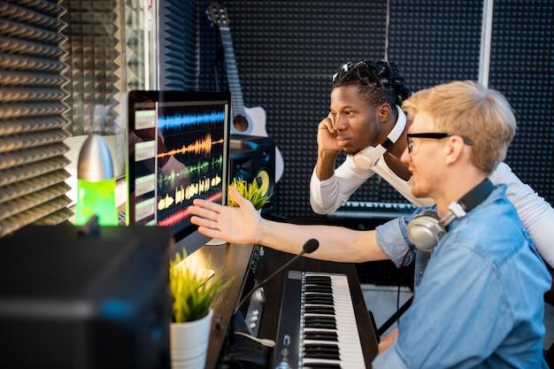 Junger afrikanischer musiker, der schallwellenformen auf computerbildschirm betrachtet, während sein kollege auf einen von ihnen im studio zeigt