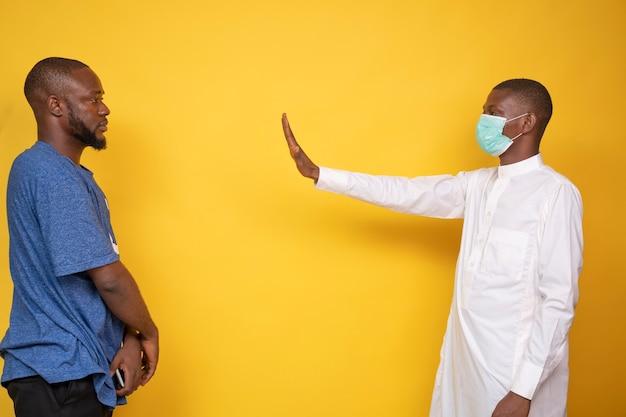 Junger afrikanischer muslimischer mann, der eine gesichtsmaske trägt und sich von einem anderen jungen mann mit einer stopp-geste distanziert