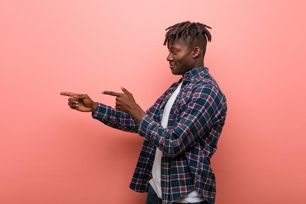 Junger afrikanischer schwarzer mann aufgeregt, zeigend mit den zeigefingern weg.
