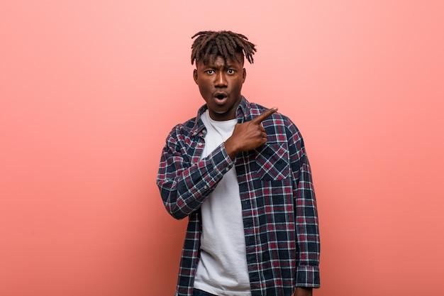 Junger afrikanischer schwarzer mann, der auf die seite zeigt