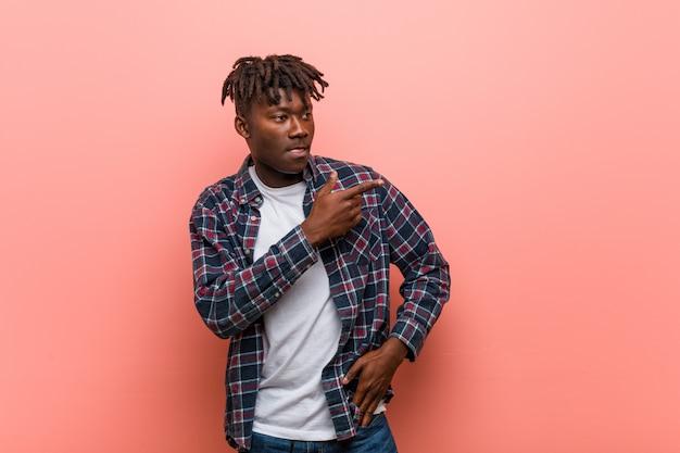 Junger afrikanischer schwarzer mann, der beiseite auf etwas, etwas zeigend lächelt und zeigt