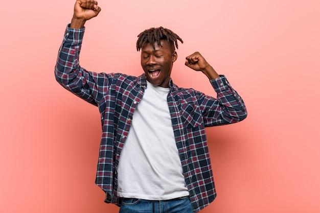 Junger afrikanischer schwarzer mann, der einen speziellen tag feiert, arme mit energie springt und anhebt.