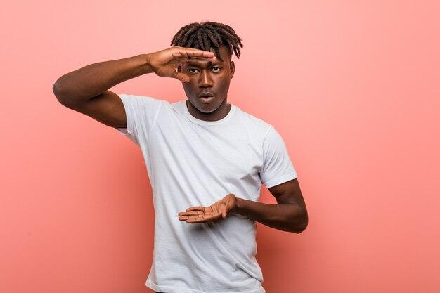 Junger afrikanischer schwarzer mann, der etwas mit beiden händen, produktdarstellung hält.