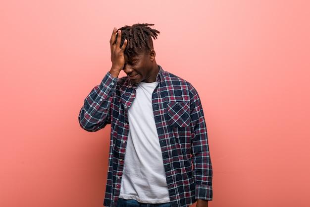 Junger afrikanischer schwarzer mann, der etwas vergisst, stirn mit palme schlägt und augen schließt.