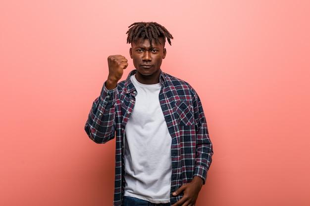Junger afrikanischer schwarzer mann, der faust zur kamera, aggressiver gesichtsausdruck zeigt.