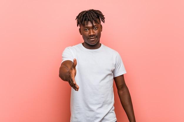 Junger afrikanischer schwarzer mann, der hand an der kamera in der grußgeste ausdehnt.