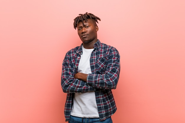 Junger afrikanischer schwarzer mann, der in camera mit sarkastischem ausdruck unglücklich schaut.