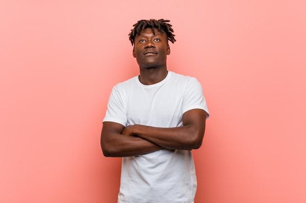 Junger afrikanischer schwarzer mann, der mit den gekreuzten armen überzeugt lächelt.