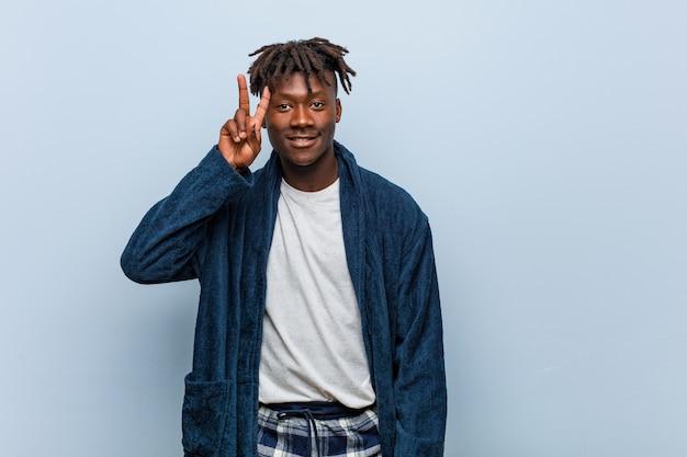 Junger afrikanischer schwarzer mann, der pyjama trägt, das siegeszeichen zeigt und breit lächelt.