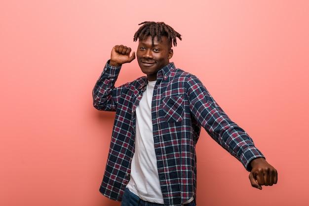 Junger afrikanischer schwarzer mann, der spaß tanzt und hat.