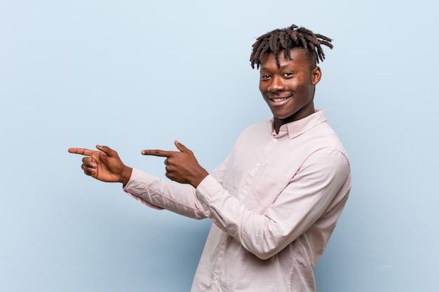 Junger afrikanischer schwarzer mann des geschäfts aufgeregt, zeigend mit den zeigefingern weg.