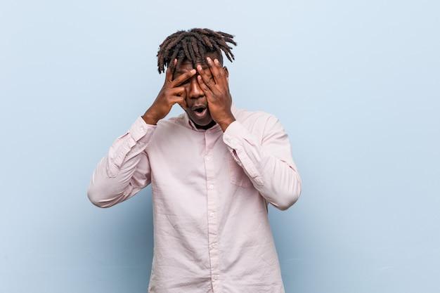 Junger afrikanischer schwarzer mann des geschäfts blinken durch die finger, die erschrocken und nervös sind.