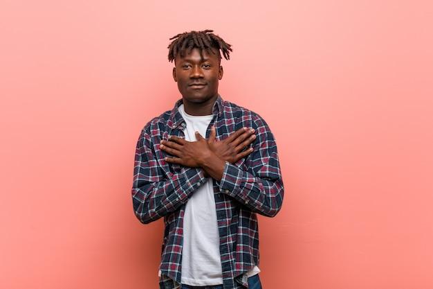 Junger afrikanischer schwarzer mann hat den freundlichen ausdruck und drückt palme zur brust. liebes-konzept.