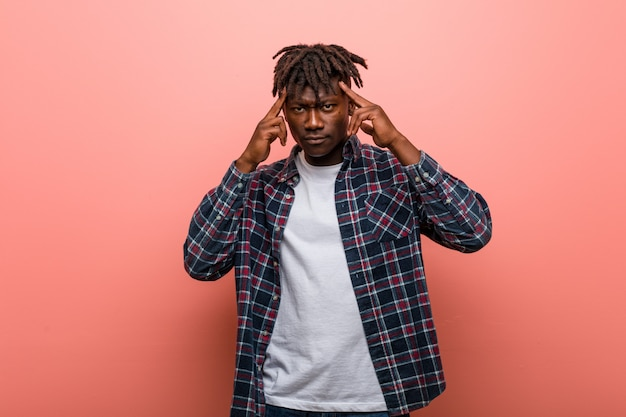 Junger afrikanischer schwarzer mann konzentrierte sich auf eine aufgabe und hielt ihn die zeigefinger, die kopf zeigen.