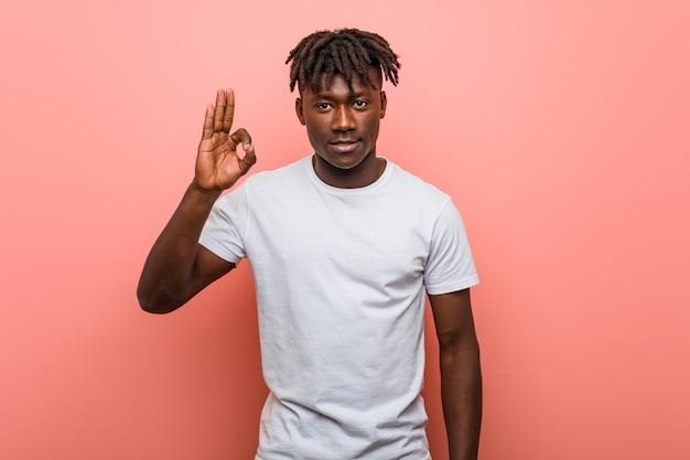 Junger afrikanischer schwarzer mann nett und überzeugt, okaygeste zeigend.