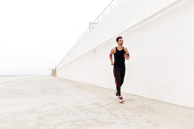 Junger afrikanischer sportmann, der draußen läuft.