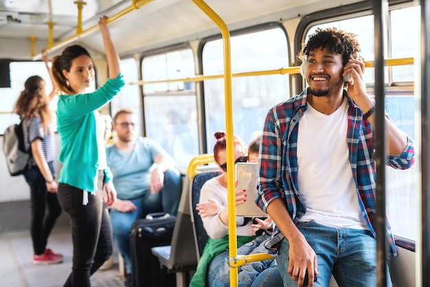 Junger afrikanischer typ, der die musik hört, während in den öffentlichen verkehrsmitteln reitend.