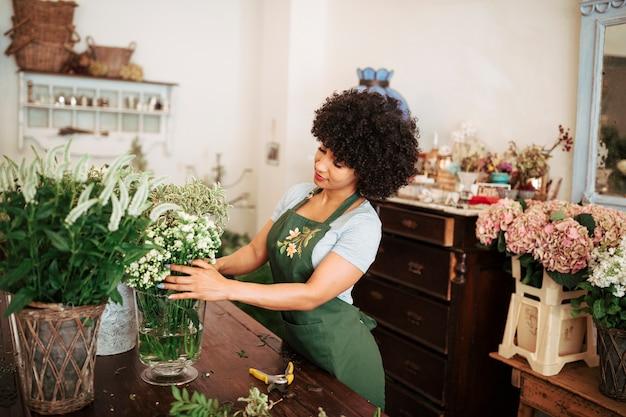 Junger afrikanischer weiblicher florist, der blumen im shop anordnet