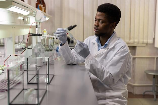 Junger afrikanischer wissenschaftler, der vor der injektion einen neuen impfstoff in eine spritze nimmt