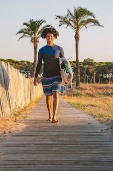 Junger afro-latino-surfer geht mit einem surfbrett bei sonnenaufgang den holzsteg zum strand hinunter
