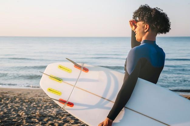 Junger afro-latino-surfer mit surfbrett am strand bei sonnenaufgang
