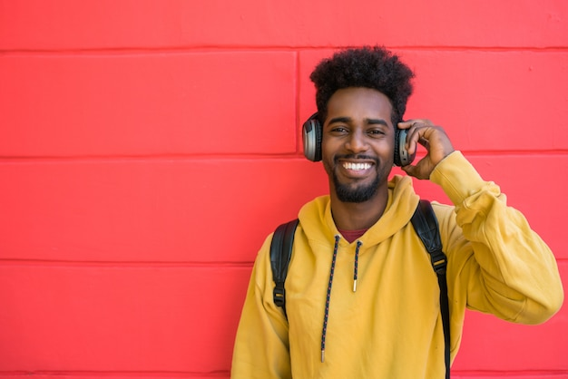 Junger afro-mann, der musik mit kopfhörern hört.