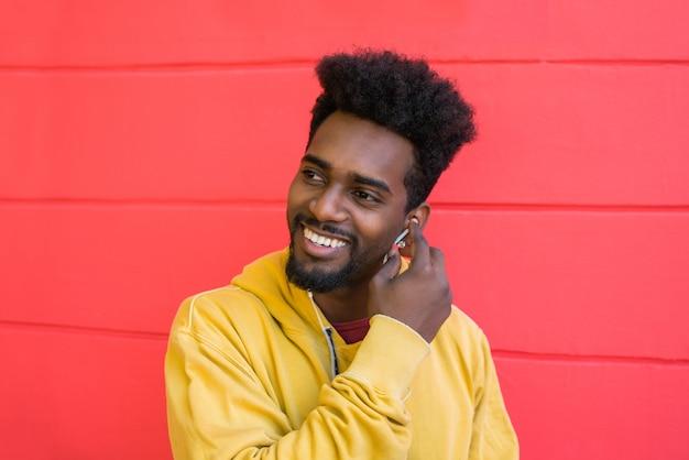 Junger afro-mann, der musik mit kopfhörern hört